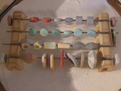 batch of bisque beads, coated with glaze and waiting to be fired in the kiln.