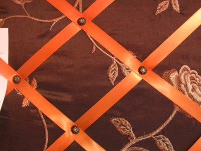Close up of board showing ribbon placement and decorative upholstery tacks.