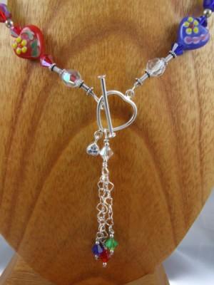Close up of multi-hued heart necklace by Lynn Smythe