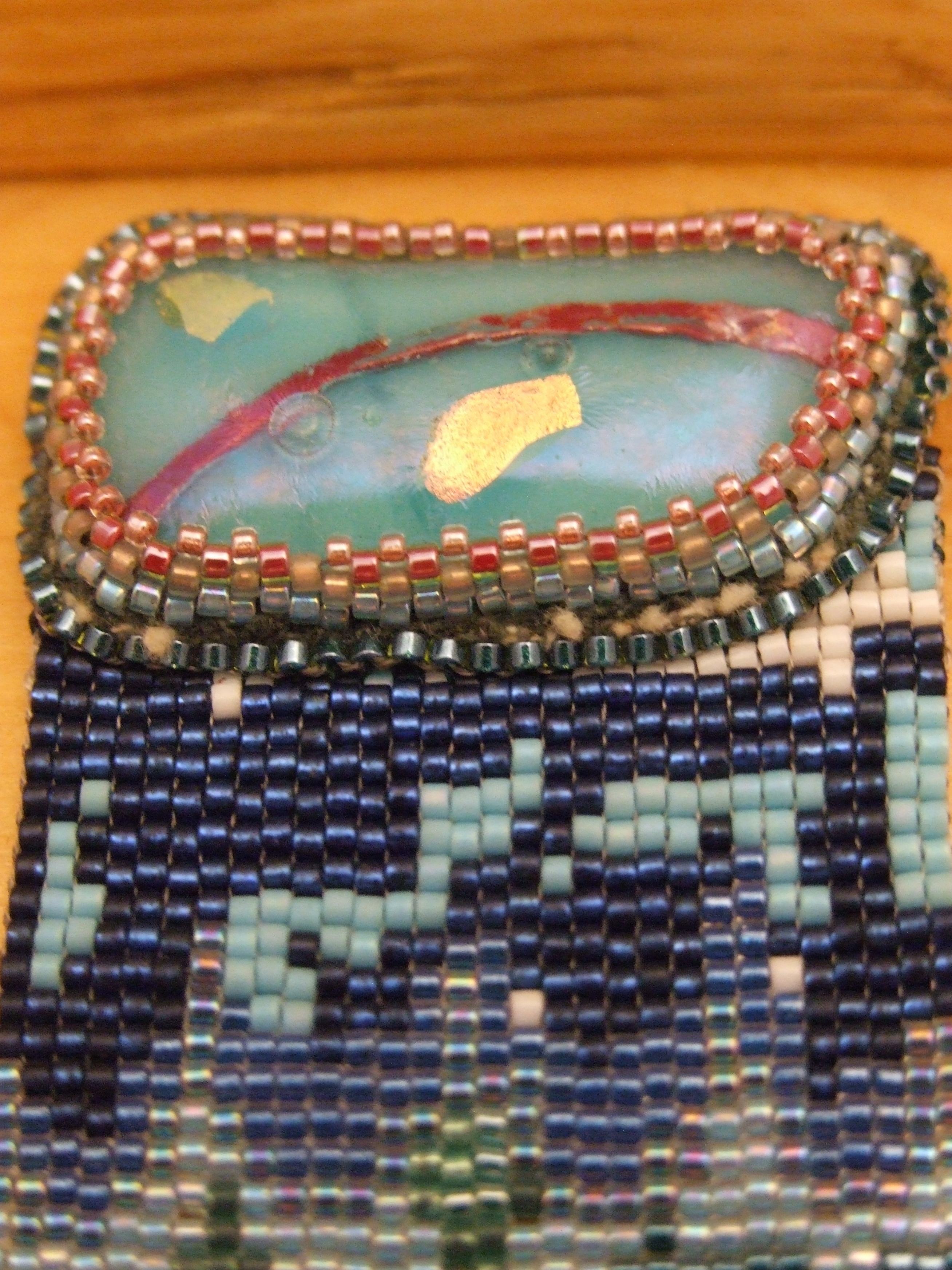 Close-up of Under the Sea loom woven bracelet by Lynn Smythe featuring one of her fused glass cabochons with captured copper embellishment.